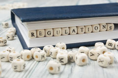 Regulations word written on wood block. Wooden ABC.  Stock Images