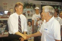 Regulatorn Bill Clinton skakar händer med ägaren av den Parma Peiroges restaurangen under den Clinton/levrat blodBuscapade aktion Arkivbilder
