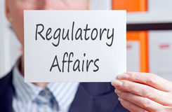 Regulatory affairs. A businesswoman holding up a sign Regulatory Affairs Stock Photography
