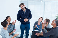 Rehab group applauding delighted man standing up Stock Photo