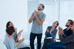 Rehab group applauding delighted man standing up Stock Image