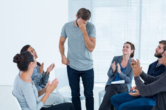 Rehab group applauding delighted man standing up Stock Images