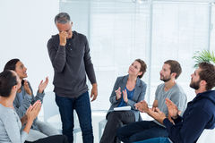 Rehab group applauding delighted man standing up. Rehab group applauding delighted men standing up at therapy session Stock Photo
