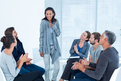 Rehab group applauding delighted woman standing up. Rehab group applauding delighted women standing up at therapy session Royalty Free Stock Image