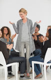 Rehab group applauding smiling woman standing up Stock Photo