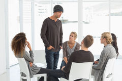 Rehab group listening to man standing up introducing himself Royalty Free Stock Photography