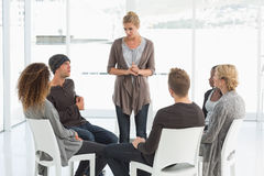 Rehab group listening to woman standing up introducing herself Royalty Free Stock Image