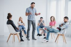 Rehab specialist and rebellious teenagers. Rehab specialist conversing with a group of rebellious teenagers sitting in a circle Royalty Free Stock Image