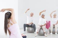 Rehabilitation on exercise balls. Three seniors in sportswear during rehabilitation on grey exercise balls Stock Photography