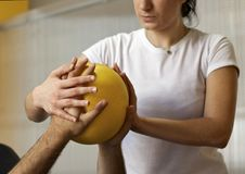 Rehabilitation practice with ball. Hands on ball. Young female physiotherapist training with colleague. Practice hand therapy with yellow ball. Hands crossed on Stock Photography