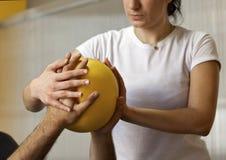 Rehabilitationspraxis mit Ball Hände auf Ball Stockfotografie