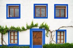 Rehabilitierte Hausfassade mit blauen Fenstern Stockfoto