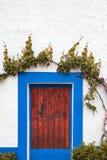 Rehabilitierte Hausfassade mit blauen Fenstern Stockfotografie