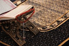Rehal with open Quran and prayer beads on Muslim prayer mat.