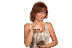 Reheaded Woman Money Jar. Smiling freckled redhead drops money into a clear glass savings jar as a financial banking concept Stock Photography
