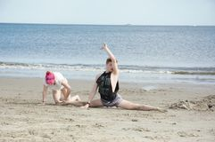 Two dancers on a beach. Two young dancers rehearsing on a beach with the sea in the background Stock Photography