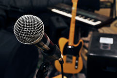 Rehearsal room. In a rehearsal room from a pop band. a microphone in the front. in the background a guitar and a keyboard are visible Royalty Free Stock Photography