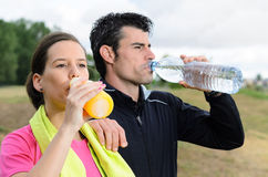 Rehydratation couple. Young sport couple drinking water and isotonic drink after trainning Royalty Free Stock Photo