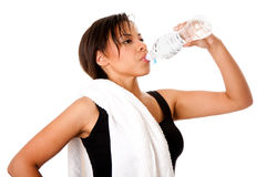 Rehydrating drinking water after workout. Beautiful attractive young sweaty woman drinking water after exercise workout, rehydrating thirst quenching, isolated Stock Images