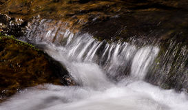 Reißender Fluss-Flüsse unter Steinen stockbilder