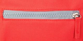 Reißverschluss auf einem roten Hintergrund. stockfotografie