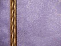 Reißverschluss auf violettem Gewebeabschluß oben, als Hintergrund stockfotografie