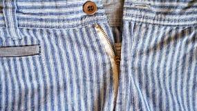 Reißverschluss und Knopf auf blauer Anlage stockbild