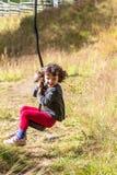 ReißverschlussLine Reiten des kleinen Mädchens in überwuchertem Spielplatz stockfoto
