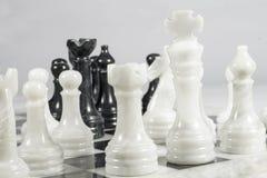 Rei branco ameaçado em um jogo de xadrez A jogada da rainha Partes e tabuleiro de xadrez de mármore Imagens de Stock