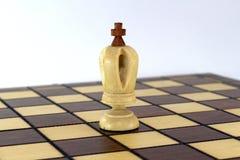 Rei branco da xadrez solitária em um tabuleiro de xadrez sobre o fundo branco Fotos de Stock Royalty Free