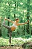 Rei da ioga da pose da dança pela mulher na grama verde no parque Imagens de Stock