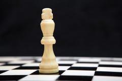 Rei e tabuleiro de xadrez brancos em um fundo preto Fotos de Stock Royalty Free