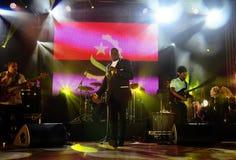 Rei Helder, Stadiums-Musiker, Angola-Flaggen-Hintergrund, tanzend lizenzfreie stockbilder
