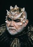 Rei mau do submundo com os espinhos na barba do cara e a branca que veste o equipamento metálico escuro isolado no fundo preto imagem de stock