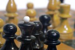 Rei preto da xadrez cercado por seus penhores no fundo do ot Imagem de Stock