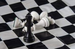 Rei preto que está no tabuleiro de xadrez, rei branco da xadrez caído com fotos de stock