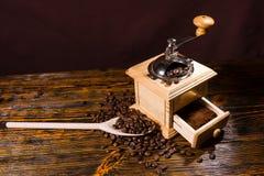Reibende Röstkaffee-Bohnen mit Handschleifer lizenzfreie stockfotos