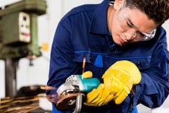 Reibendes Metall der asiatischen Arbeitskraft in der Produktionsanlage lizenzfreies stockfoto