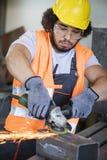 Reibendes Metall des jungen Arbeiters in der Industrie lizenzfreie stockfotos