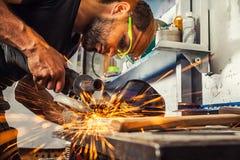 Reibendes Metall des Mannes mit einem Winkelschleifer Stockfotos