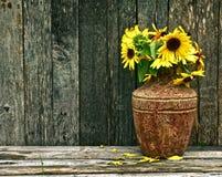 Reich getonte Sonnenblumen auf Holz. stockbild
