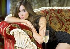 Reiche Frau auf einem roten teuren Sofa Stockfotografie