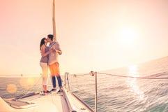Reiche junge Paare in der Liebe auf dem Segelboot, das bei Sonnenuntergang zujubelt lizenzfreie stockfotos