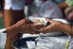 Reiche Leute geben den Armen Lebensmittel Verhungernkonzept stockbild