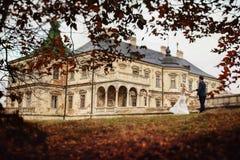Reiche pflegen sich und Braut huggingoutdoor Hintergrund-Wandgras wärmen a Lizenzfreies Stockbild
