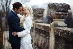 Reiche pflegen sich und Braut huggingoutdoor Hintergrund-Wandgras wärmen a Stockbilder