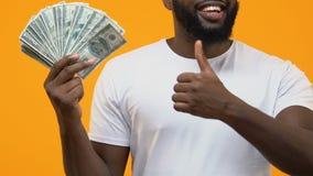 Reicher afroer-amerikanisch Mann, der Dollar auf dem gelben Hintergrund, eigenhändig zeigend hält stock footage