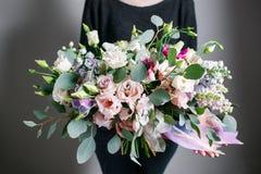 Reicher Blumenstrauß, grüner frischer Frühlingsblumenstrauß des Blattes in der Hand Blaues Meer, Himmel u Stockfoto