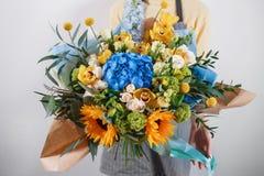 Reicher Blumenstrauß, grüner frischer Frühlingsblumenstrauß des Blattes in der Hand Blaues Meer, Himmel u Lizenzfreie Stockfotos