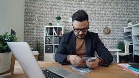 Reicher Unternehmer, der das lächelnde Sitzen des Geldes am Bürotisch bei der Arbeit zählt stock video